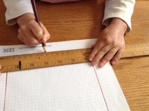 using a ruler and pencil to mark on graph paper