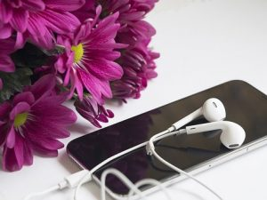 iPhone with headphones and flowers